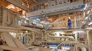 Bilden tagen inne i det flytande kärnkraftverket. På bilden syns en person och en massa rör i olika våningar.