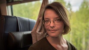 kvinna med glasögon sitter på tåg