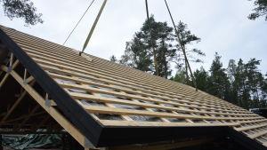 Takstolar på marken hopbyggt till ett färdigt tak. Ska just lyftas av en kran.