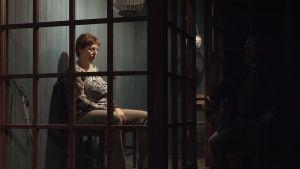 Mari Turusen näyttelemä nainen, Maura, istuu synkkänä lasitetulla terassilla.