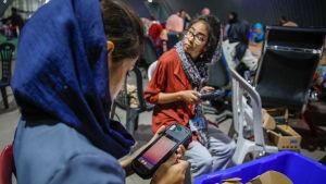 Två afghanska kvinnor som arbetar som valfunktionärer  granskar biometriska apparater som används i det afghanska presidentvalet i slutet av september 2019