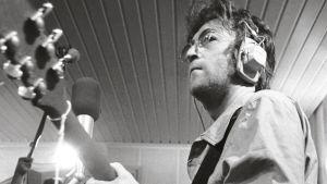 John Lennon studiossa 1971, kitara kädessä, kuulokkeet korvilla.
