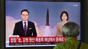 En sydkoreansk man framför en Nordkoreansk nyhetssändning var de berättar om missiltestet.
