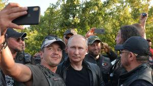 Mies ottaa itsestään ja Vladimir Putinista kuvaa Applen kännykällä.