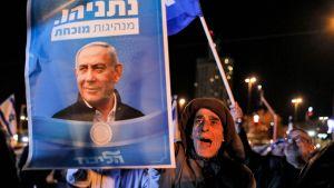 En man håller i en valplansch med ett foto på Israels premiärminister Benjamin Netanyahus  ropar slagord