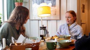 Madde och Ida tittar på varandra vid frukostbordet.