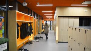 orange skolkorridor, lärare går i korridoren