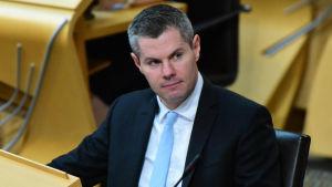 Derek Mackay, en medelålders man i blå kostym och kort grått hår sitter i sal med många stolar.