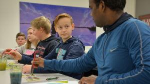 Elever och Venkat sitter vid ett bord och målar. Den ena pojken tittar på Venkat.