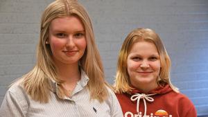 Två elever står och ler bredvid varandra i sitt klassrum i Prakticum.