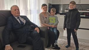 Man sitter på en soffa, bredvid soffan sitter en kvinna med en pojke i famnen. Bredvid kvinnan står en litet äldre pojke. I bakgrunden syns ett kök.