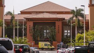 En stor orange byggnad som blivit avspärrad av polisband. Framför byggnaden står en polisbil och en ambulans parkerade.