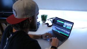 En man med keps på huvudet sitter framför en dator.