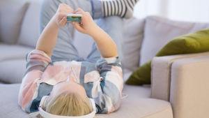 En flicka ligger i soffan och lyssnar på musik