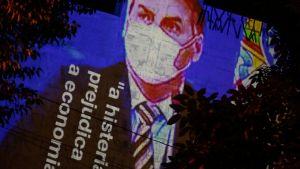 En bild på Brasiliens president JAir Bolsonaro projiceras på en vägg under en demonstration mot presidentens coronapolitik