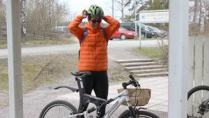 kvinna sätter på sig cykelhjälm