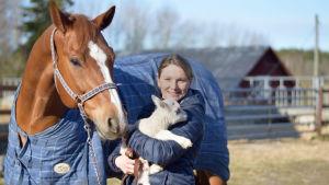 Jessica Aminoff håller i ett får brevid en häst