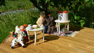 En Pippi-docka, ett Mumintroll-gosedjur och två dockor är placerade på ett brunnslock ute i en trädgård.