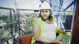 Programvärd Joel Forsbacka sitter i ett Pariserhjul med byggarbetskläder på.