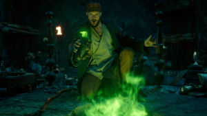 På bilden syns Gustaf Skarsgård i rollen som trollkarlen Merlin. Här står han knäböjd i ett mörkt rum med sin käpp bredvid sig och framför honom syns grön rök.