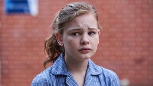 Huolestuneen näköinen 12-vuotias transtyttö katsoo vasempaan.