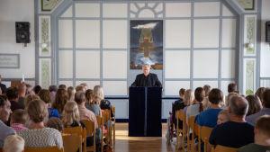 Lestadiolainen seurakunta istuu jumalanpalveluksessa, heidän edessään seisoo pappi.