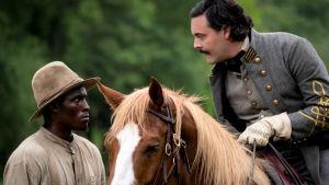 Jack Hustons brutala plantage-herre lutar sig över en svart arbetare från sin hästrygg.