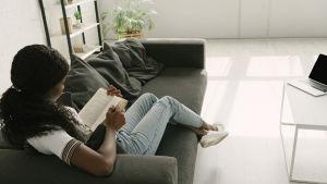 En kvinna ligger i en soffa och läser en bok.