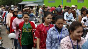 Kvinnor står i en kö utanför en fabrik i Kambodja. De är klädda i färggranna kläder.