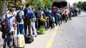 Flyktingar som köar till en buss på Lesbos