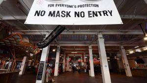 """""""Inget munskydd - ingen entré"""" står det vid ingången till en marknad i Los Angeles, USA 30.11.2020"""