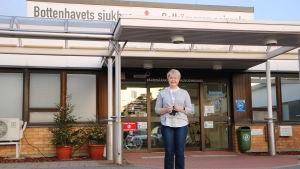 En kvinna med kort blont hår står framför ingången till en hälsovårdscentral.