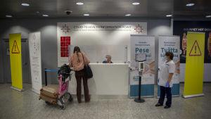 En resenär söker sig till coronatest på flygplatsen. I bild resenären som fyller i lappar vid en disk, en som väntar på att ta testet och en man som sitter bakom disken.