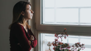 Kvinna i profil framför fönster