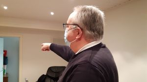 Kenneth Lindvall med corona-munskydd pekar mot en öppen dörr