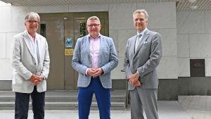 Tre kavajklädda män utanför en bank (Ekenäs Sparbank).