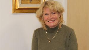 blond kvinna sitter på ett bord framför en tavla, hon ler