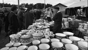 Svartvit bild av en försäljare på en marknad. På bordet står olika slags emaljskålar.