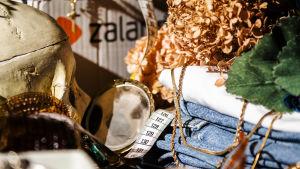 Bildkollage på kläder, accessoarer, ett postorderpaket och ett måttband.