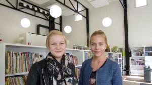 Två glada tonårsflickor framför vita bokhyllor med böcker.