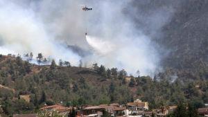En helikopter fäller vatten över skogsbranden i byn Eyrixou, Cypern 20.6.2016