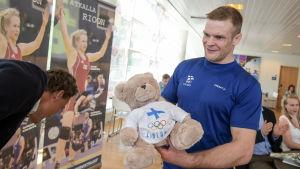 Tero Välimäki håller i en teddybjörn vid ett pressinfo inför OS i Rio.