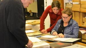 Ortsborna Rauno Nikkanen, Riikka Niemistö och Arja Aminoff studerar arkiv.