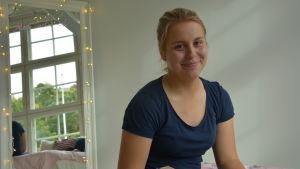 Ung tjej ler mot kameran då hon sitter på sitt rum vid i en nödinkvartering.