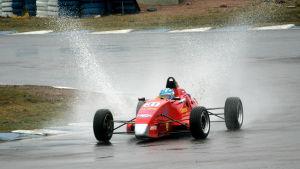 Formula-auto ajaa märällä radalla.