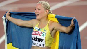 Mora Hjelmer firar omsvept av den svenska flaggan.