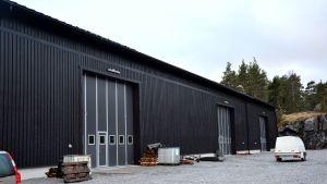 Baggö Marinas båtförvaringshall, en stor, svart byggnad i trä.