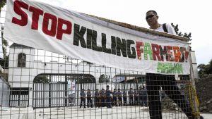 """En banderoll med texten """"Sluta mörda jordbrukare"""" i samband med en demonstration mot undantagstillståndet i Mindanao, utanför ett militärhögkvarter i Quezon City 6.12.2017."""