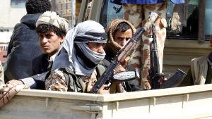 Rebeller i Jemen sitter på ett bilflak med stormgevär i famnen.
