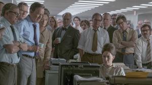 Redaktionen på Washington Post står alla samlade kring ett bord och tittar på tv-nyheterna.